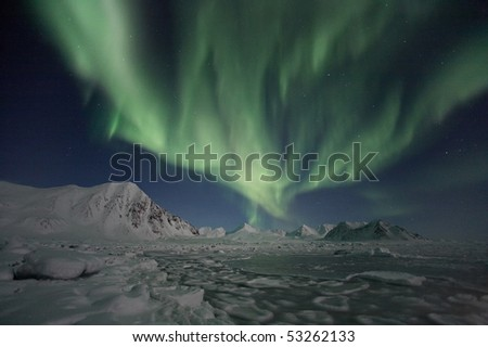 Outstanding Northern Lights above Svalbard mountains - stock photo
