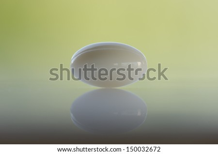 Oval pill against green background - stock photo