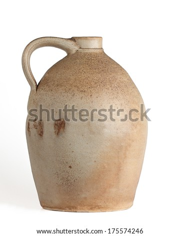 Oval shaped tan and yellow clay jug with handle, white background, profile view. - stock photo