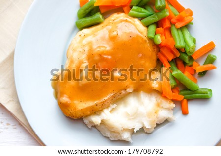 Oven baked chicken in gravy with mashed potatoes and vegetables  - stock photo