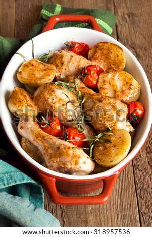 Oven baked chicken legs with vegetables (tomatoes, potatoes), herbs and spices in baking dish on rustic wooden background - stock photo