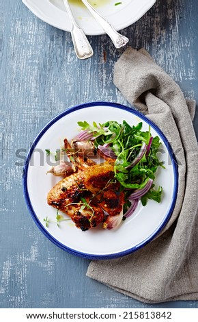 Oven-baked chicken wings with arugula salad - stock photo