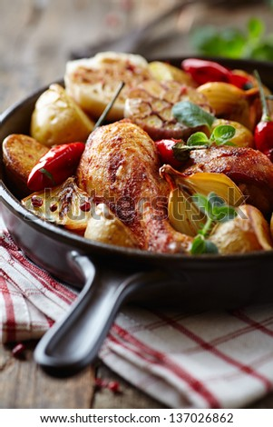 Oven-baked chicken with vegetables and herbs - stock photo