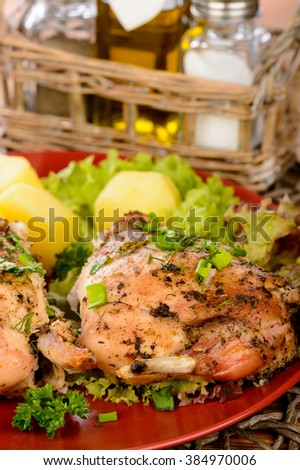 Oven baked rabbit with potatoes on red plate on wooden table. - stock photo