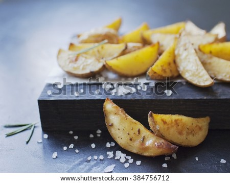 oven baked spicy potato slices on wooden desk served on paper with sea salt, and rosemary