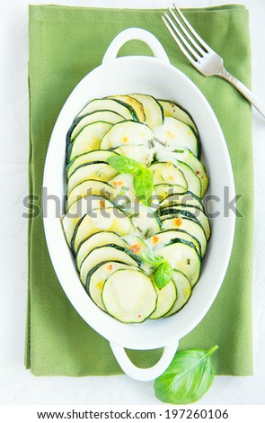 oven baked zucchini with mozzarella cheese and basil leaves in ceramic white dish - stock photo