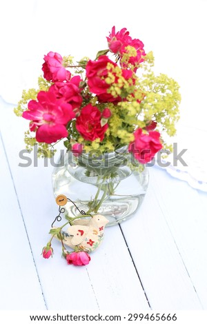 Over exposed  Re-cycled glass jar with wild red roses and green Lady's Mantle flowers , with shabby chic   bird ornament on pale blue wooden floorboards, summer outdoor wedding  pretty arrangement,  - stock photo