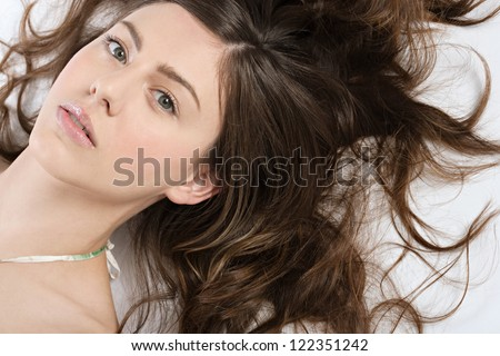 Over head beauty close up portrait of an attractive hispanic young woman lying down on the floor with her curly hair spread around her head. - stock photo