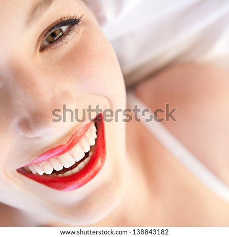 Over head beauty portrait of a young woman's half face laying down in bed wearing white lingerie and red lips, smiling at the camera. - stock photo