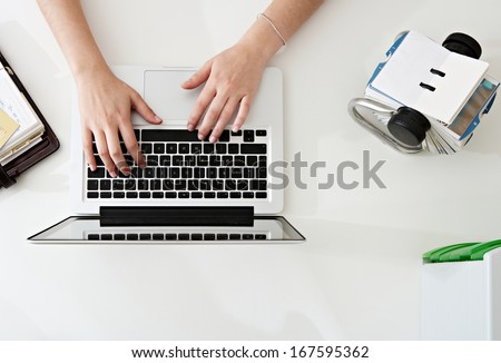 Over head close up detail view of a professional woman hands typing on a laptop computer while making a payment on line with a credit card while at an office desk, workplace interior. - stock photo