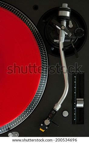 Over head close up detail view of a record player with a red vinyl album, interior. Still life professional musical equipment objects. - stock photo