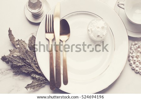Over head flat lay view of elegant white and gold fine china. Gold flatware, pearls, diamond, snowflakes, glittered leaves and dishes. Wedding background.