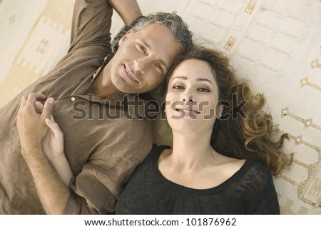 Over head portrait of a mature man and woman laying down on carpet, holding hands and smiling at camera. - stock photo