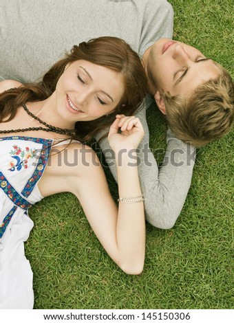 Over head portrait view of a young couple laying down on green grass in a park, relaxing and lounging together and smiling happy. - stock photo