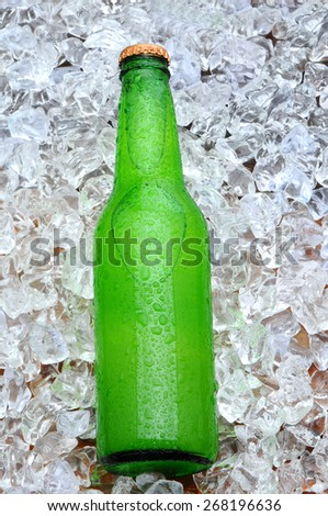 Over head shot of a bottle of lemon lime soda laying on a bed of ice. The bottles os covered with condensation.  - stock photo