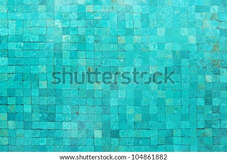 Over head view of a blue swimming pool with mosaic tiles and still water.