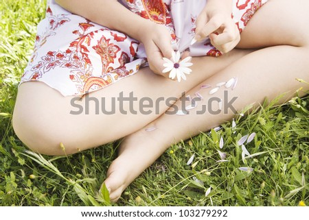 Over head view of a girl pulling off the petals of a daisy flower.