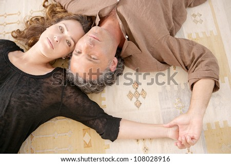 Over head view of a mature couple laying down on carpet at home. - stock photo