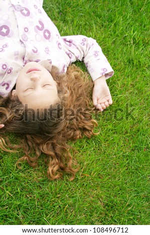 Over head view of a young girl laying down on green grass with her eyes shut. - stock photo