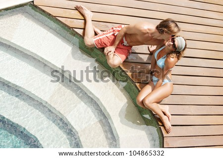 Over head view of an attractive couple kissing while they relax by a swimming pool's steps in a hotel garden. - stock photo