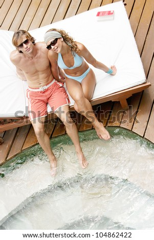 Over head view of an attractive couple sunbathing and being affectionate while sitting by a swimming pool's steps in a hotel garden.