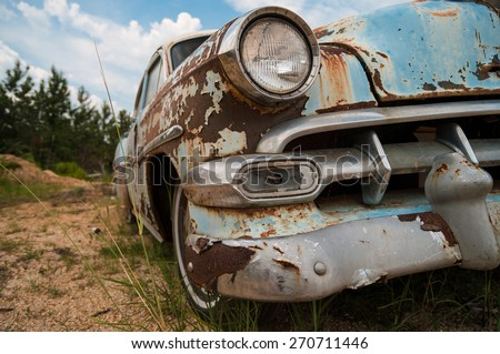 Over Parked. Rusted, classic car sits broken down in a sandy lot with trees and clouds in the distance. - stock photo