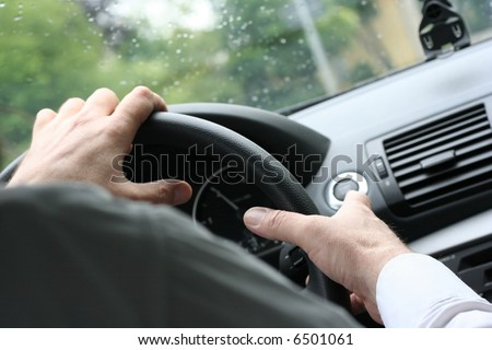 Over shoulder view of a man driving a car with his hands on the steering wheel. (Rainy Weather) - stock photo