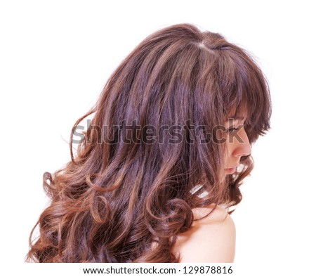 Over the shoulder side view studio portrait of a pensive young woman with beautiful long wavy auburn hair - stock photo
