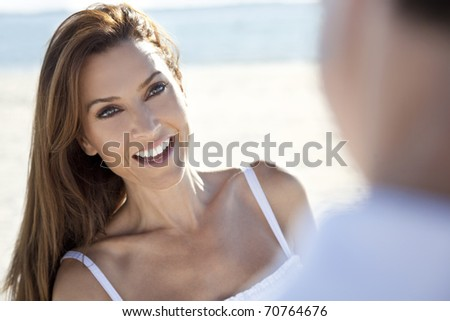 Over the shoulder view of a beautiful woman laughing and having fun with a man as a romantic couple on a beach - stock photo