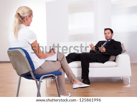 Over the shoulder view of a business man reclining comfortably on a couch talking to his psychiatrist explaining something - stock photo