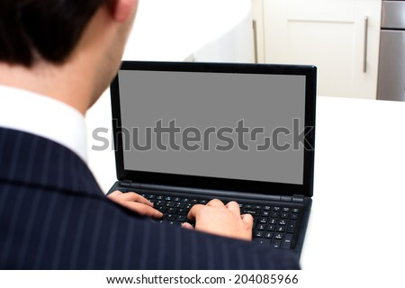 Over the shoulder view of a businessman working at a laptop with a view of the blank screen with copyspace for your text or advertisement - stock photo
