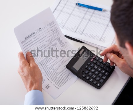 Over the shoulder view of a man checking an invoice on a calculator - stock photo