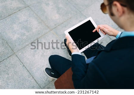 Over the shoulder view of man working on digital tablet, focus on tablet - stock photo