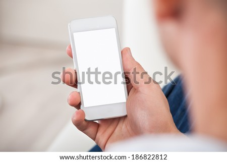Over the shoulder view of the blank screen on a smartphone or mobile phone held in a mans hand - stock photo