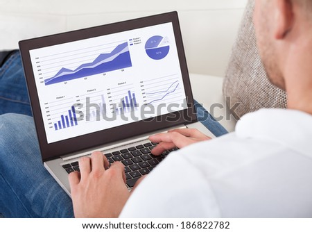 Over the shoulder view of the screen of a businessman analyzing graphs on his laptop - stock photo
