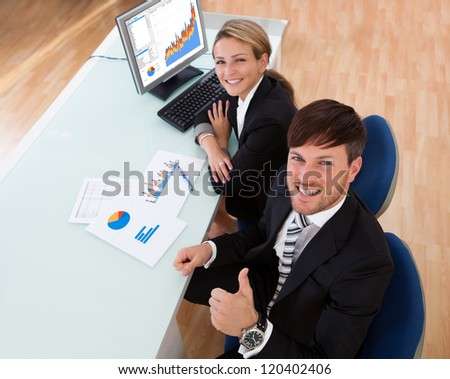 Over the shoulder view of two business partners discussing a colorful fluctuating bar graph comparing it with a text table - stock photo