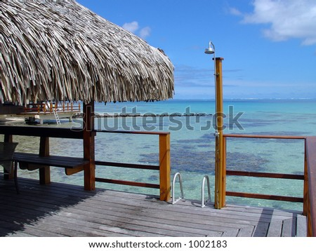 Over-water bungalow outside deck with outdoor shower, a ladder into the clear blue water and a view of the South Pacific.