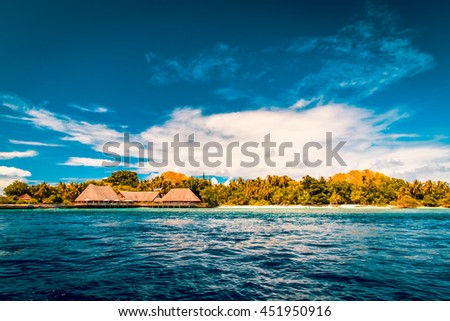 Over water bungalows on a tropical island with palm trees and amazing beach in Maldives. Summer travel holiday background.
