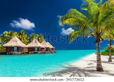 Over water bungalows on a tropical island with palm trees and amazing vibrant beach - stock photo