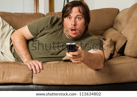 Over weight man watching something shocking on TV. Could it be tabloids, celebrity gossip, a movie, or something else? - stock photo