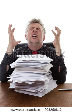 over worked businessman with a stack of paper work  infront of him sitting on his desk - stock photo