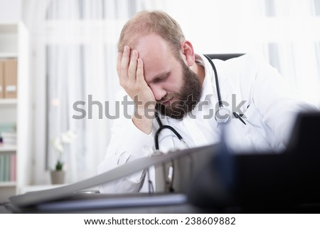 Over worked doctor sitting at desk - stock photo