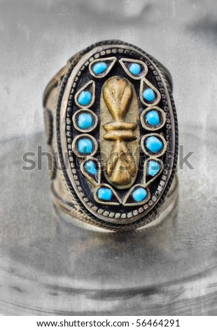 over 100 years old antique Turkish tribal ring with grunge pattern and blue stones on textured background.