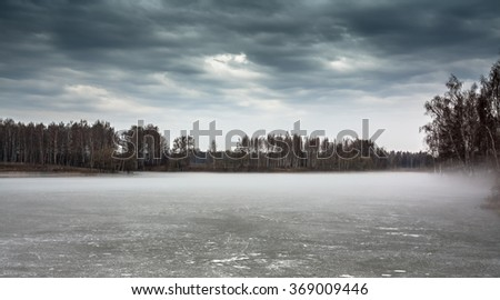 Overcast landscape on frozen misty lake  and moody sky in period between spring and winter - stock photo