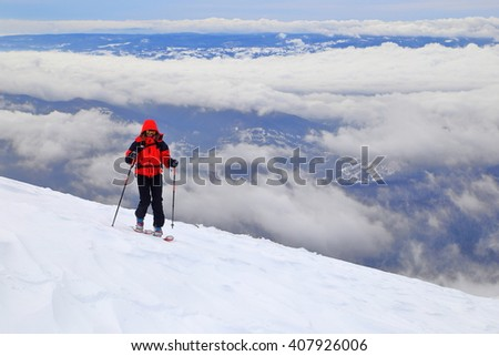 Overcast weather and woman skier traversing a slope on touring skis above the clouds - stock photo