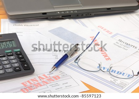 Overdue Bills with Calculator and Laptop - stock photo