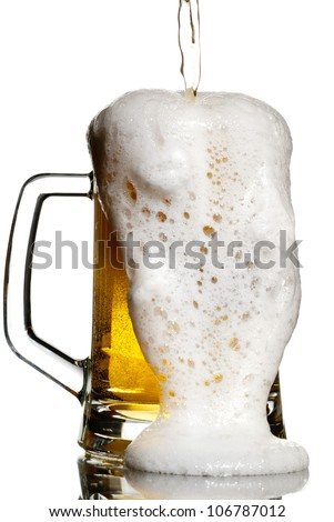 Overflowing beer from a heavy keg isolated on white