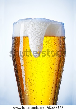 overflowing beer glass with a bit of condensation - stock photo