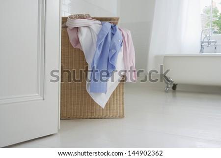 Overflowing wicker laundry basket in bathroom - stock photo