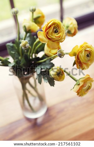Overhead angled view of vase of yellow vintage roses flowers - stock photo